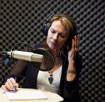 Woman working on podcast in front of microphone.